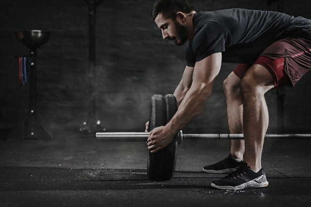 Jonge cross fit atleet barbell voorbereiden op het tillen van gewicht in de sportschool