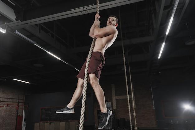 Jonge crossfit-atleet die een touw beklimt in de sportschool. man doet functionele training. trainingsoefeningen