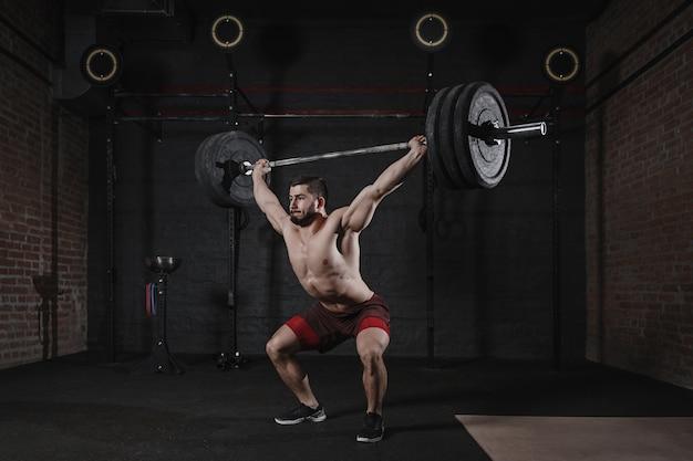 Jonge crossfit-atleet die zware barbell boven het hoofd opheft in de sportschool. knappe man functionele training doet. powerlifting oefenen.