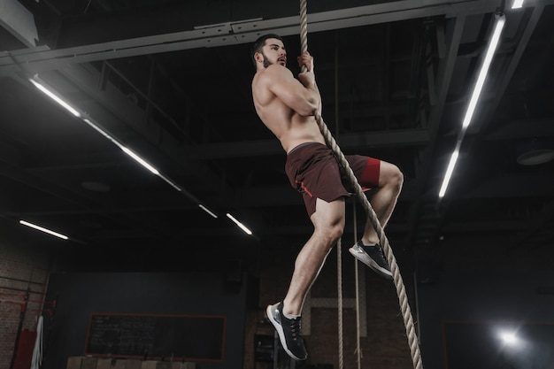 Jonge crossfit atleet een touw klimmen in de sportschool