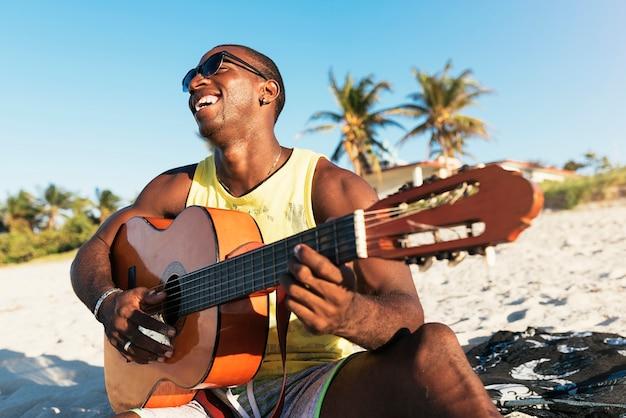 Jonge cubaanse man die plezier heeft op het strand met zijn gitaar. vriendschapsconcept.