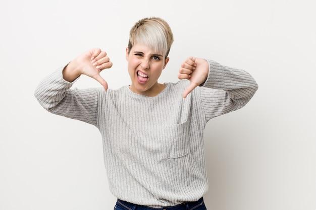Jonge curvy kaukasische die vrouw op wit wordt geïsoleerd die duim tonen en afkeer uitdrukken.