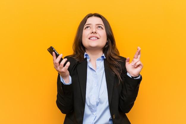 Jonge curvy plus grootte bedrijfsvrouw die een telefoon houden die vingers kruisen voor het hebben van geluk