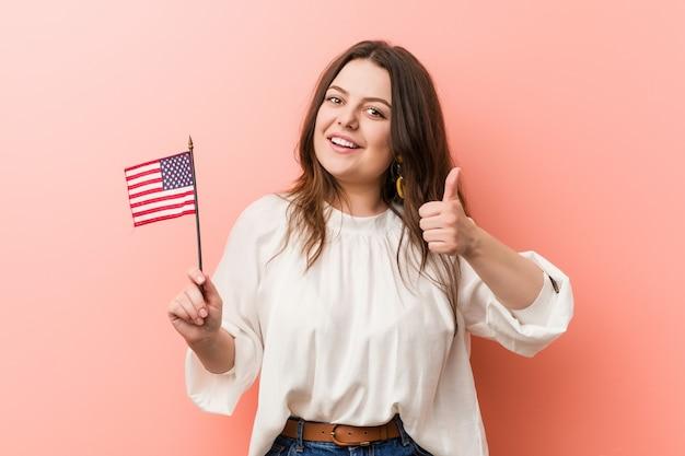 Jonge curvy plus groottevrouw die een vlag houden die van verenigde staten en duim opheffen glimlachen