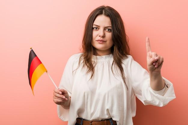 Jonge curvy plus groottevrouw die een vlag van duitsland houden die nummer één met vinger toont.