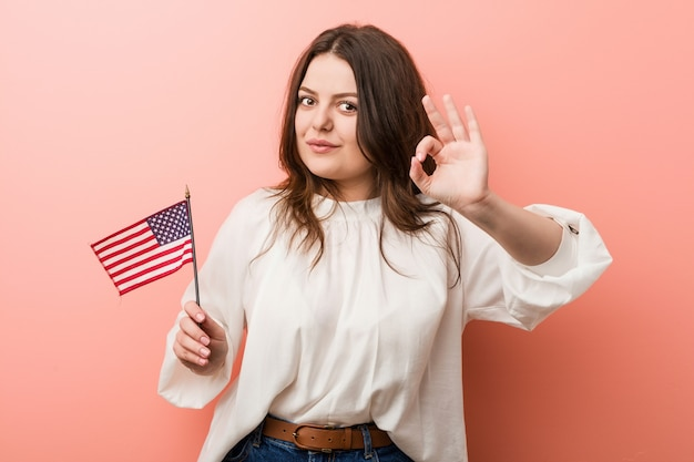 Jonge curvy plus groottevrouw die een vlag vrolijk en zeker houden die van verenigde staten ok gebaar tonen.