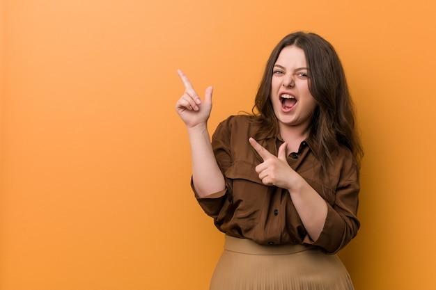 Jonge curvy russische vrouw die met wijsvingers aan een exemplaarruimte richt, opwinding en wens uitdrukt.