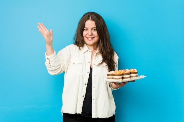 Jonge curvy vrouw die cupcakes houdt die een prettige verrassing ontvangt, opgewekte en handen opheft.