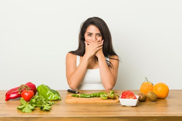 Jonge curvy vrouw die een gezonde geschokte maaltijd voorbereidt behandelend mond met handen