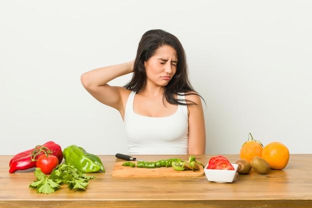 Jonge curvy vrouw die een gezonde maaltijd voorbereidt die aan nekpijn lijdt wegens sedentaire levensstijl.