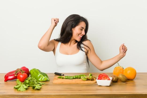 Jonge curvy vrouw die een gezonde maaltijd voorbereidt die en pret danst heeft.