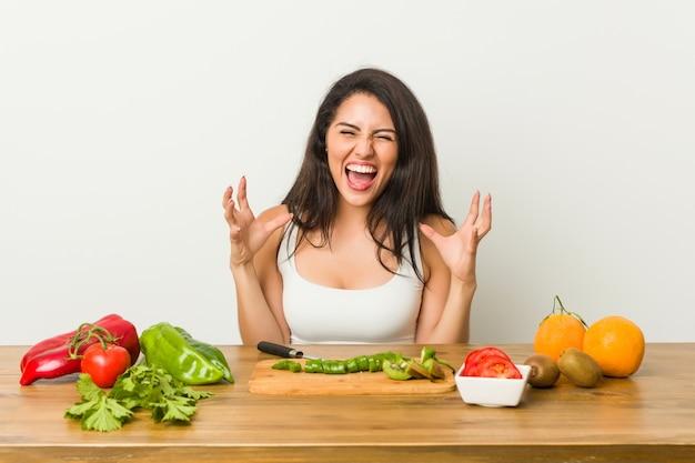Jonge curvy vrouw die een gezonde maaltijd voorbereidt die met woede gilt.