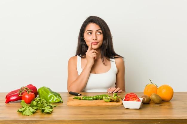 Jonge curvy vrouw die een gezonde maaltijd voorbereidt die zijdelings met twijfelachtige en sceptische uitdrukking kijkt.
