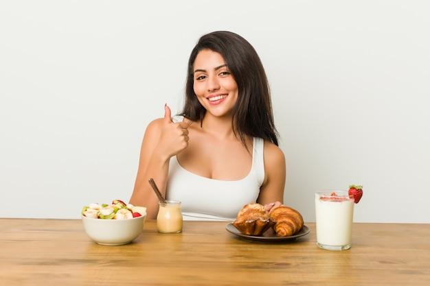 Jonge curvy vrouw die een ontbijt neemt dat en duim opheft opheft