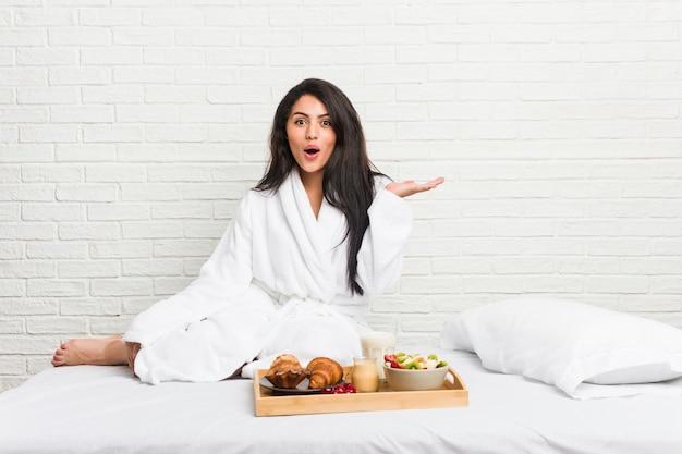 Jonge curvy vrouw die een ontbijt op het bed neemt indruk op het exemplaarruimte van de holding op palm.