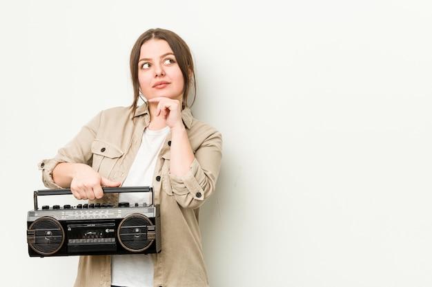 Jonge curvy vrouw die een retro radio houdt die zijdelings met twijfelachtige en sceptische uitdrukking kijkt.