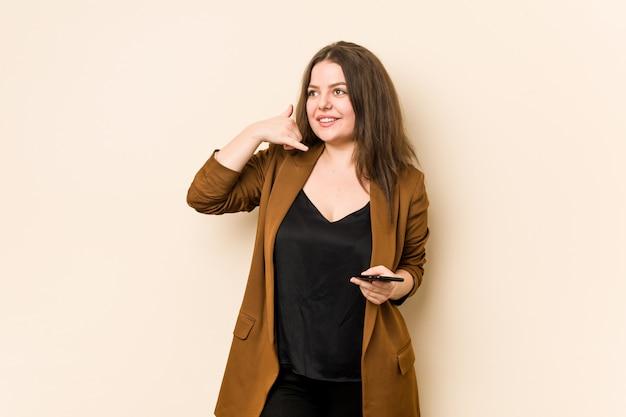 Jonge curvy vrouw die een telefoon houdt die een mobiel telefoongesprekgebaar met vingers toont.