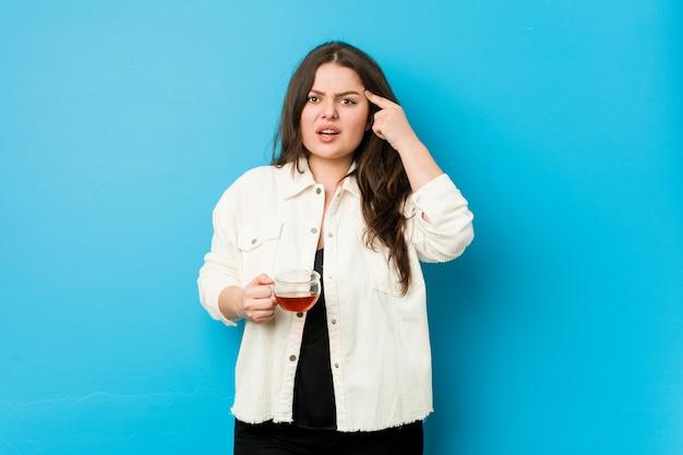 Jonge curvy vrouw die een theekop houdt die een teleurstellingsgebaar met wijsvinger toont.