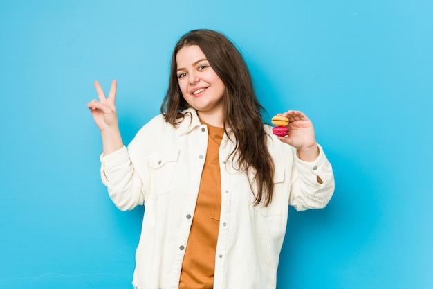 Jonge curvy vrouw die makarons blij en onbezorgd het tonen van een vredessymbool met vingers houden.