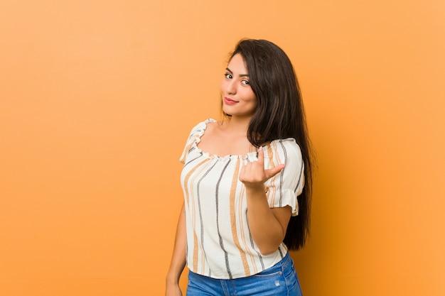 Jonge curvy vrouw die met vinger op u richt alsof uitnodigend dichterbij kom.