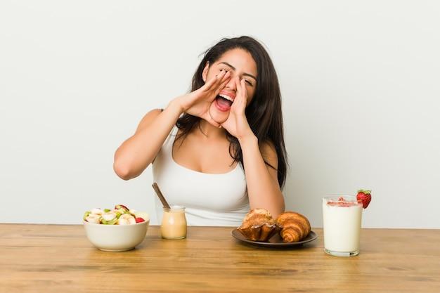 Jonge curvy vrouw die ontbijt schreeuwen opgewekt neemt aan voorzijde uit.