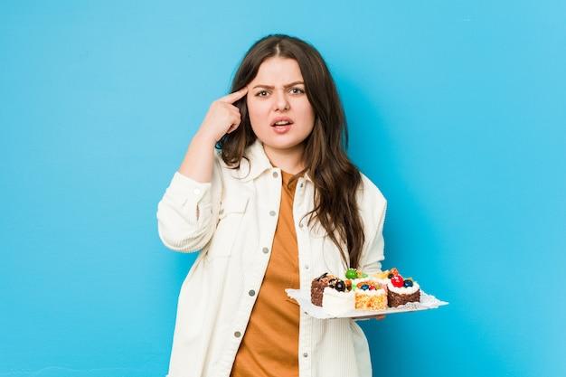 Jonge curvy vrouw die zoete cakes houdt die een teleurstellingsgebaar met wijsvinger tonen.