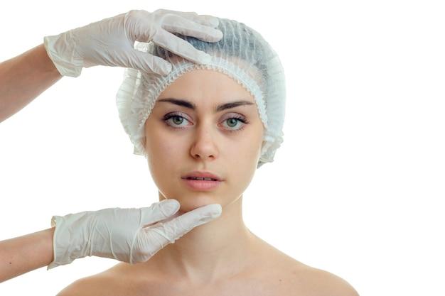 Jonge cutievrouw bij de plastische chirurg die op witte muur wordt geïsoleerd