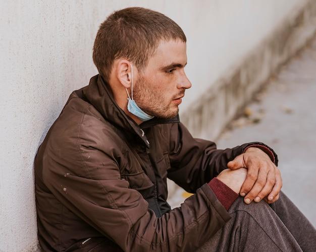 Jonge dakloze man op straat met medische masker
