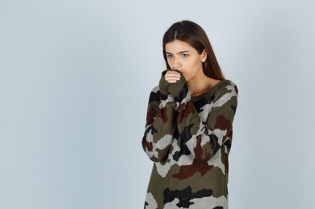 Jonge dame ademt op haar handen om ze warm te houden in trui, rok en onwel