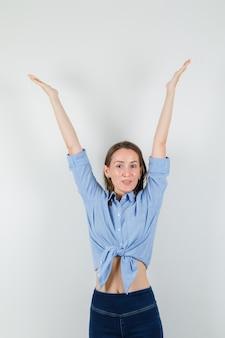 Jonge dame armen in blauw shirt, broek strekken en op zoek gelukkig