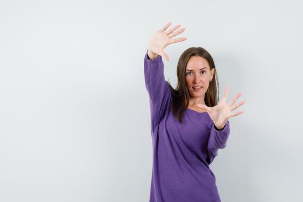 Jonge dame armen strekken en palmen in violet overhemd vooraanzicht tonen.