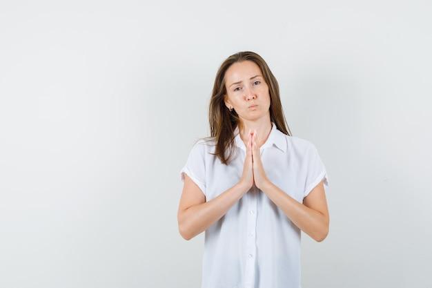 Jonge dame bidden gebaar in witte blouse tonen en wenselijk op zoek.