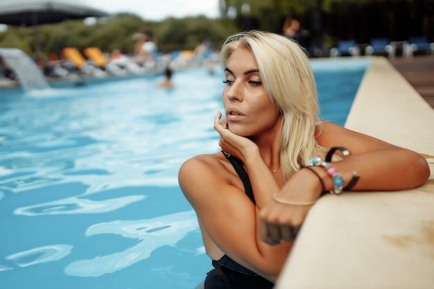 Jonge dame bij zwembad. zomervakantie bij het zwembad
