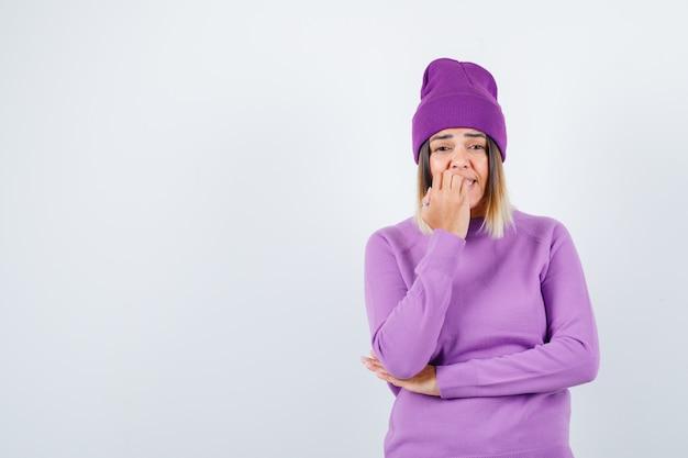 Jonge dame bijt haar nagels in paarse trui, muts en kijkt opgewonden, vooraanzicht.