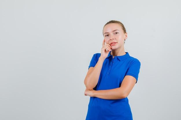 Jonge dame camera in blauw t-shirt kijken en vrolijk kijken
