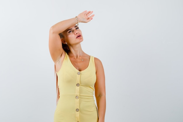 Jonge dame die aan hoofdpijn in gele kleding lijdt en pijnlijk, vooraanzicht kijkt.