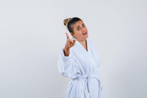 Jonge dame die camera in badjas richt en er schattig uitziet