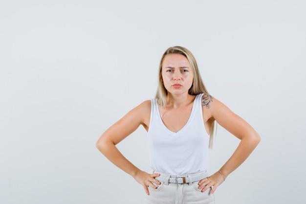 Jonge dame die camera in witte blouse bekijkt en ongelukkig kijkt
