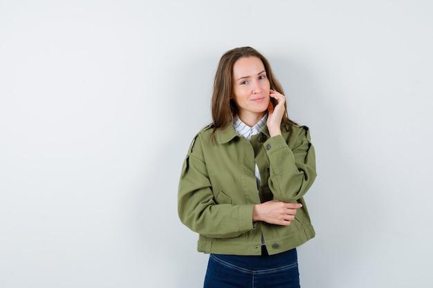 Jonge dame die de gezichtshuid op haar wang aanraakt in blouse, jas en er elegant uitziet, vooraanzicht.