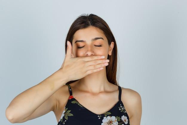 Jonge dame die de hand op de mond houdt in een blouse en er vredig uitziet. vooraanzicht.