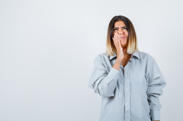 Jonge dame die de hand op de wang houdt terwijl ze opkijkt in een oversized shirt en er attent uitziet, vooraanzicht.