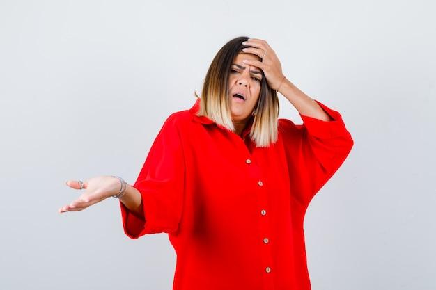 Jonge dame die de hand op het hoofd houdt terwijl ze de palm opzij spreidt in een rood oversized shirt en er angstig uitziet, vooraanzicht.