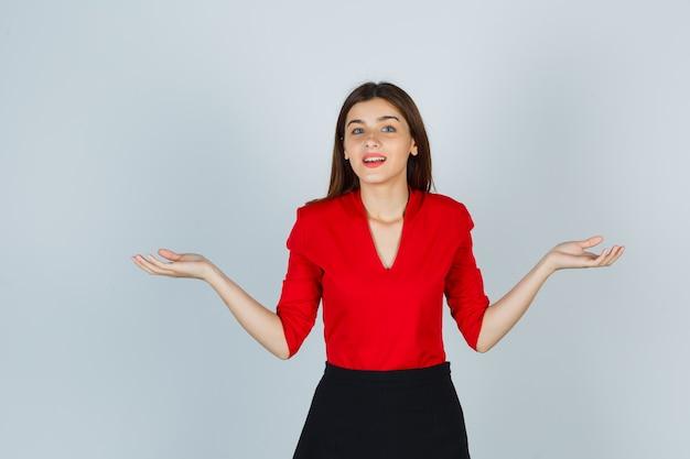 Jonge dame die de handpalmen opzij spreidt in een rode blouse, rok en er vrolijk uitziet