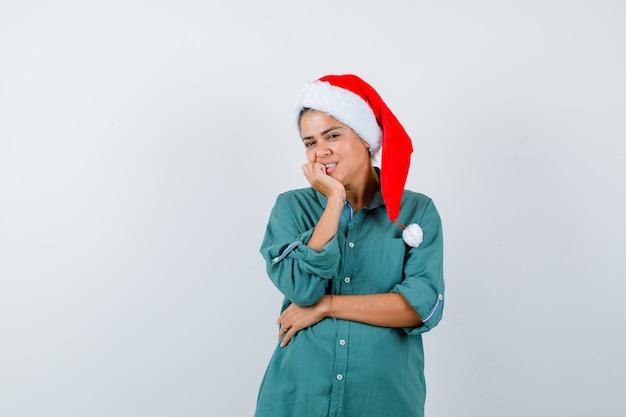 Jonge dame die de kin bij de hand steekt in een kerstmuts, een shirt en er vrolijk uitziet, vooraanzicht.