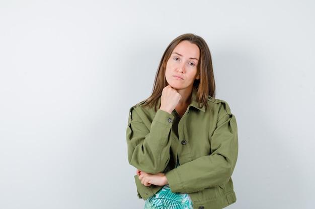 Jonge dame die de kin op de vuist steekt in blouse, jas en peinzend kijkt, vooraanzicht.
