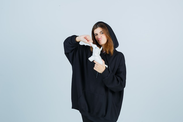Jonge dame die de speelgoedkoffer van een olifant trekt terwijl ze lippen pruilt in een oversized hoodie, broek en verbaasd kijkt. vooraanzicht.