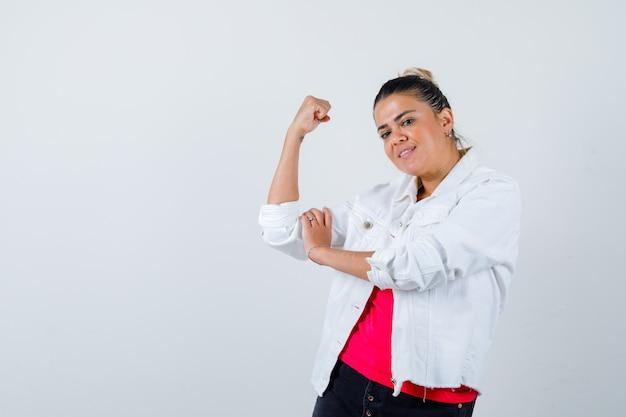 Jonge dame die de spieren van de arm in t-shirt, witte jas toont en er vrolijk uitziet, vooraanzicht.