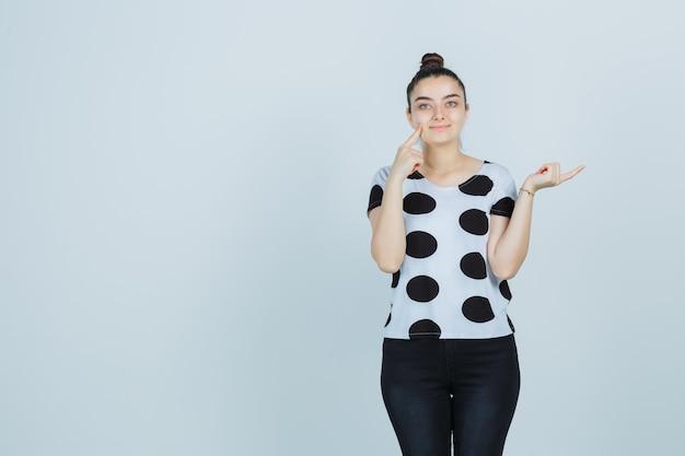 Jonge dame die de vinger op de wang drukt terwijl ze naar de rechterkant wijst in een t-shirt, spijkerbroek en er zelfverzekerd uitziet. vooraanzicht.