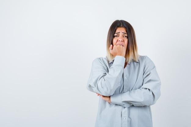 Jonge dame die de vuist op de mond houdt in een te groot shirt en er bang uitziet, vooraanzicht.
