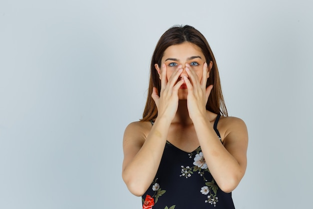 Jonge dame die doet alsof ze een gezichtsmasker rond de neuszone in de blouse wrijft en er charmant uitziet. vooraanzicht.